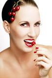 Beautiful woman eating a cherry. Beautiful woman with cherries in her hair, red lipstick and red-violet make-up. She's eating a cherry Stock Image