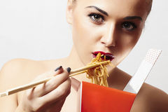 Beautiful woman eating chinese food. wok. close-up. red lips stock photography