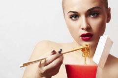 Beautiful woman eating chinese food. wok. close-up. red lips Stock Images