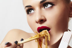 Beautiful woman eating chinese food. wok. close-up. red lips stock photo