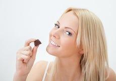 Beautiful woman eating chocolate Stock Photos