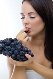 Beautiful woman eating fresh grapes Royalty Free Stock Image
