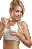 Beautiful woman eating fresh yogurt for breakfast Stock Photography