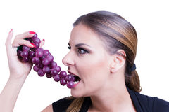 Beautiful  Woman eating grapes Stock Images