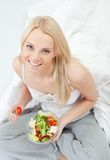 Beautiful woman eating green salad Stock Images