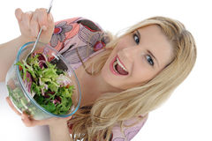 Beautiful woman eating green vegetable salad royalty free stock images