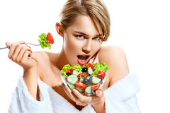 Beautiful woman eating healthy food. Photo of blonde woman in bathrobe isolated on white background. Diet. Healthy lifestyle Stock Photography