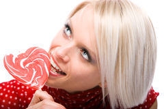 Beautiful woman eating a heart-shaped lollipop Royalty Free Stock Image