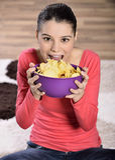 Beautiful woman eating junk food. Eating potato chips / crisps. Cute woman having a junk food snack while stock photo
