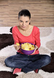 Beautiful woman eating junk food. Eating potato chips / crisps. Cute woman having a junk food snack while stock images
