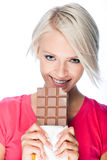 Beautiful woman eating a large bar of chocolate Royalty Free Stock Photo