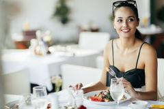 Beautiful woman eating meal in restaurant. During sunset stock photo