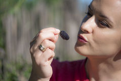 Beautiful woman eating a mulberry. Mulberry are so benefic fruits for woman health Stock Photo