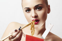 Beautiful woman are eating noodles.red lips.Chinese sticks. fast food Royalty Free Stock Image