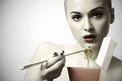 Beautiful woman are eating noodles.red lips.Chinese sticks. fast food Royalty Free Stock Photography