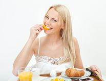 Beautiful woman eating orange in bed Royalty Free Stock Images