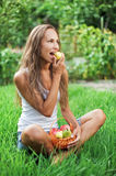 Beautiful woman eating pear on the green grass. In the garden Stock Photography