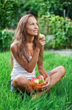 Beautiful woman eating pear on the green grass. Beautiful woman with picnic crib eating pear on the green grass stock photos