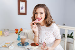 Beautiful woman eating pink heart shaped cookies Royalty Free Stock Photography