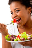 Beautiful woman eating a salad. Close up of a beautiful African woman eating a salad on an isolated background Stock Images