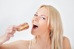 Beautiful woman eating tasty donut Royalty Free Stock Photography