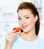Beautiful woman eating tomato Stock Photos