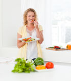 Beautiful woman is eating vegetables Royalty Free Stock Photography