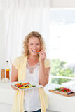 Beautiful woman is eating vegetables Royalty Free Stock Photos