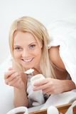 Beautiful woman eating yogurt in bed. At home Stock Images