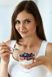 Beautiful Woman Eating Yogurt, Berries And Cereal. Healthy Diet. Healthy Eating Woman. Closeup Of Beautiful Happy Young Female Holding A Glass With Natural Royalty Free Stock Images