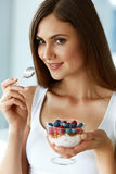 Beautiful Woman Eating Yogurt, Berries And Cereal. Healthy Diet. Healthy Eating Woman. Closeup Of Beautiful Happy Young Female Holding A Glass With Natural Royalty Free Stock Photos