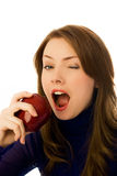 Beautiful woman eats and apple and winks Stock Image