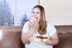 Beautiful woman eats donuts Stock Image