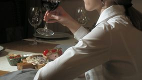 Beautiful blonde woman eating and drinking in restaurant, lunch or dinner time stock video footage