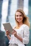 Beautiful woman with electronic tab in the street royalty free stock images