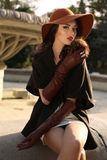 Beautiful woman in elegant coat,gloves and felt hat. Fashion outdoor photo of beautiful lady with dark hair wearing elegant coat,leather gloves and felt hat Royalty Free Stock Photography