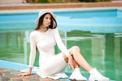 Beautiful woman in Elegant dress. brunette lying by blue swimming pool. Fashion outdoor portrait. Luxury resort. stock photography