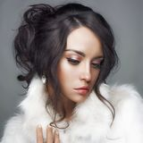 Beautiful woman with elegant hairstyle in white fur coat Royalty Free Stock Photography
