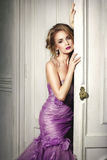 Beautiful woman in an elegant purple dress. Romantic elegant woman standing at the door Stock Image
