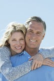 Beautiful Woman Embracing Man From Behind Against Clear Sky Stock Image