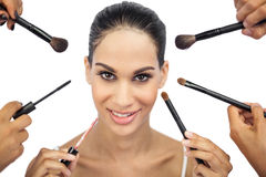 Beautiful woman encircled by make up brushes. On white background Stock Images