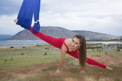 Beautiful woman engaged in antigravity yoga outdoors by the sea on the beach stock image