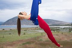 Beautiful woman engaged in antigravity yoga outdoors by the sea on the beach stock photos