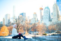Beautiful woman enjoy the view of ice-rink in Central Park and skyscrapers on Manhattan in New York City. Adorable girl in Central Park at New York City Stock Photography