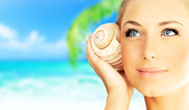 Beautiful woman enjoying beach. Closeup female face portrait, happy girl holding seashell, relaxing in nature, summer travel vacation and spa relaxation Stock Photography