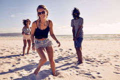 Beautiful woman enjoying on the beach with friends. Portrait of beautiful young women enjoying on the beach with friends in background. Diverse group of friends Royalty Free Stock Image