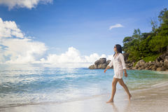 A beautiful woman walking on the beach Royalty Free Stock Photo