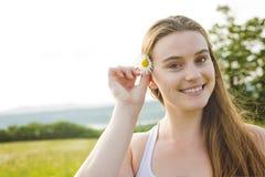 Beautiful woman enjoying daisy in a field Stock Photo