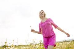 Beautiful woman enjoying daisy in a field Stock Images