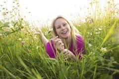 Beautiful woman enjoying daisy in a field Stock Image